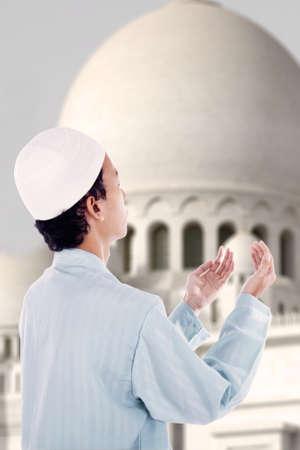 islamic prayer: Asian muslim boy is praying at mosque Stock Photo