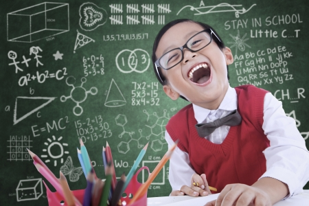 blackboard: Boy student is laughing in class while drawing something