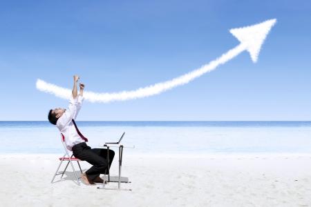 asian man laptop: Successful businessman expressing his success at the beach Stock Photo