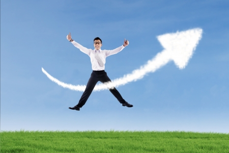 growth enhancement: Businessman jumping over success arrow cloud sign outdoor while giving hit thumbs up