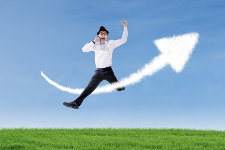 calling: Businessman is jumping and calling with his phone over up arrow sign cloud