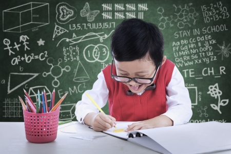 Cheerful boy student is drawing something in class photo