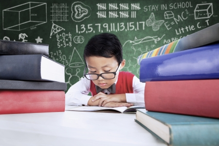 asian student: Smart student is reading books in classroom