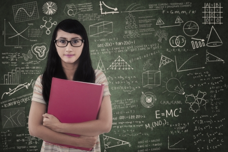 assignment: Confident female student is standing in classroom with written board