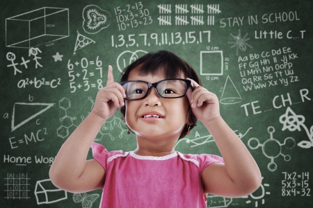 Portrait of asian female preschooler wearing glasses and rises her finger in class. photo