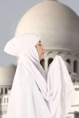 mujeres orando: Imagen de mujer musulmana en el vestido blanco rezando en la mezquita