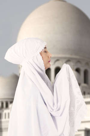 Picture of female muslim  in white dress praying at mosque photo