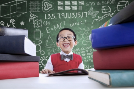 smart kid: Close-up of Asian boy laughing in class with stack of books