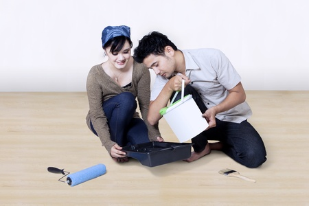 Happy Asian couple painting together at home photo