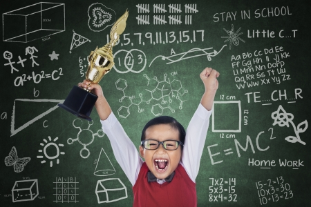 red competition: Happy student boy shouting while holding a trophy in classroom