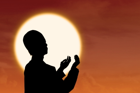 Silhouette of muslim praying at orange sunset photo