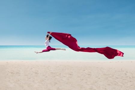 donna che balla: Incredibile ballo da danzatrice con la bandiera rossa sulla spiaggia Archivio Fotografico