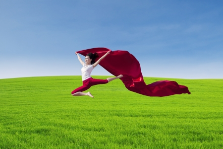 Amazing female dancer jumping with red scarf on field photo