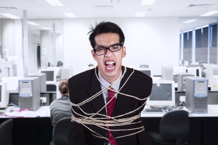 Angry businessman tied with rope at the office photo