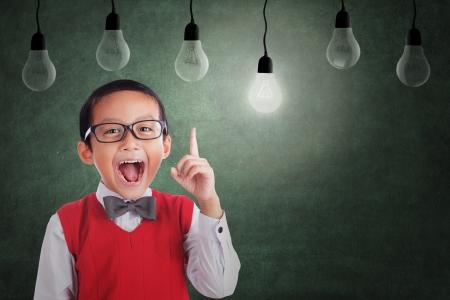 アジア学生少年クラスで電球の下で考えを持っています。 写真素材