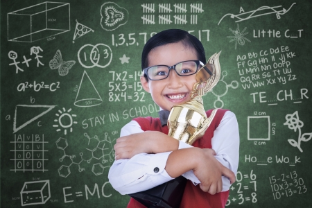 Happy Asian boy is holding trophy in classroom photo