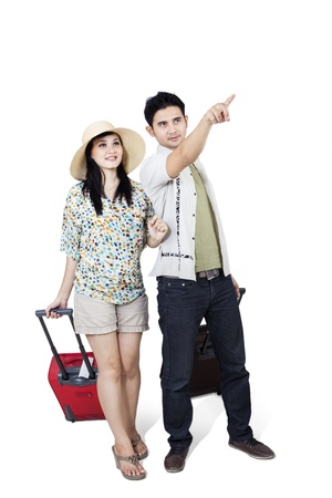 Asian couple point direction with suitcase on white background photo