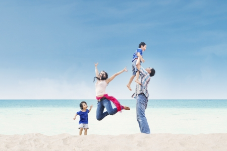the place is outdoor: Asian family having fun at the beach