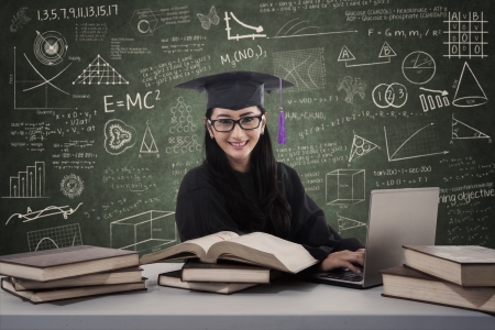 Asian female graduate is typing on laptop with books at classroom photo