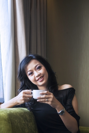 Asian female is having a coffee in her apartment photo