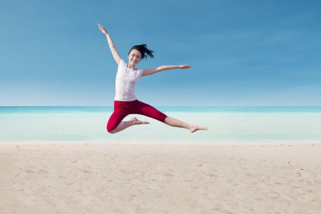 Attractive female dancer is jumping on the beach photo