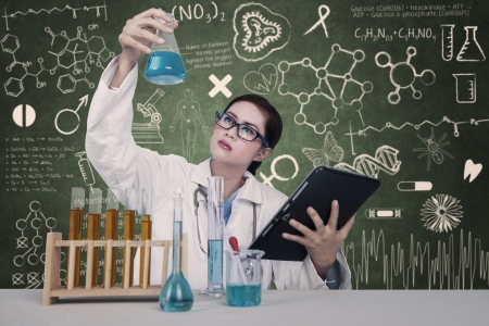 Atractive doctor examine chemical solutions at lab photo