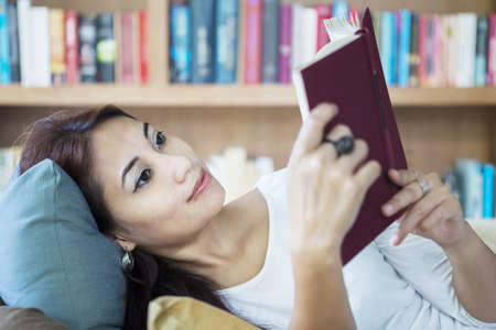 Beautiful female is reading a book in the library photo