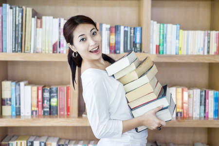 Attractive female bring stack of books in the library photo