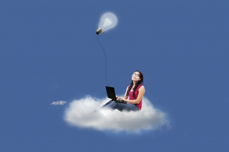 Beautiful female sitting on a cloud while using laptop under lightbulb  photo