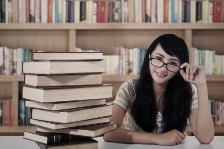 education loan: Beautiful female student sitting in the library with books
