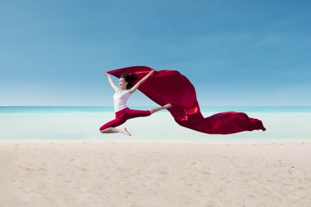 air jump: Beautiful female dancer with red flag on the beach Stock Photo