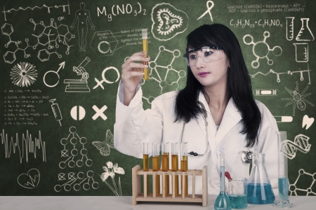 Beautiful doctor looking at liquid flasks at laboratory on written chalkboard photo
