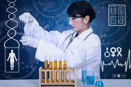 Beautiful doctor analysing liquid on blue background photo
