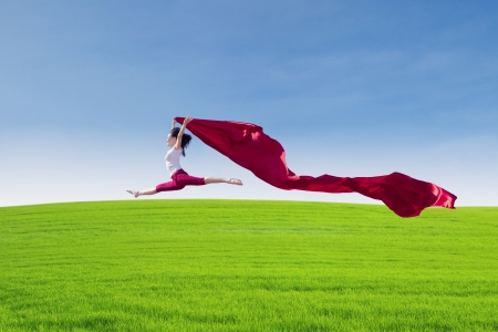 Beautiful Asian female jumping with big red scarf on green field photo
