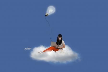 Beautiful female using laptop on cloud under bright lamp Stock Photo - 20709548