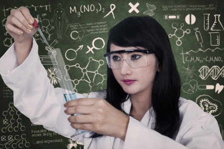 Beautiful scientist is analysing the liquid inside flask on written chalkboard background photo