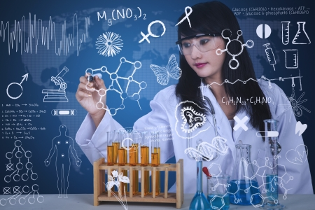 Beautiful scientist is drawing on transparant glass with flasks and blue background Stock Photo - 20709576