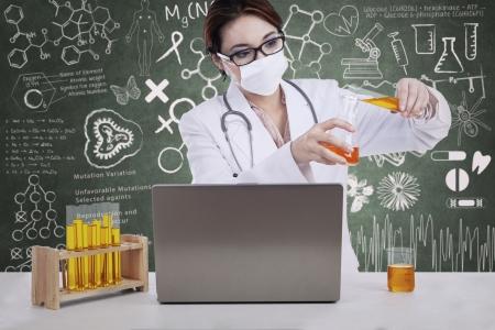 female scientist: Beautiful female scientist pour liquid to flasks with written chalkboard background