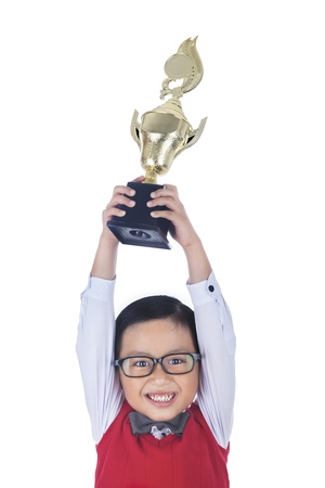 Boy is holding a trophy above his head, isolated on white photo