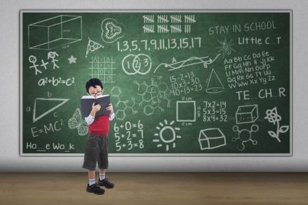 Asian boy reading book with written chalkboard, full length shot photo