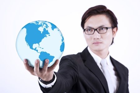 Asian businessman looking smart with glasses holding a globe on white background photo