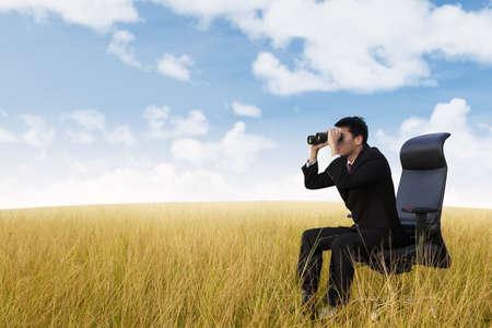 job searching: Businessman see vision using binoculars on wheat field Stock Photo
