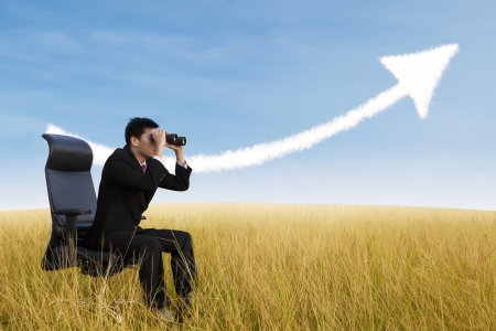 growing business: Businessman using binoculars looking for growing chart cloud on field