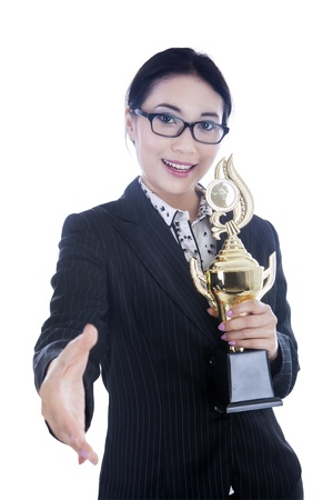 Beautiful businesswoman with open hand ready for handshake while holding trophy, isolated on white photo