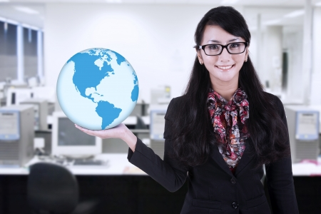 environmental suit: Businesswoman is holding blue world global at office