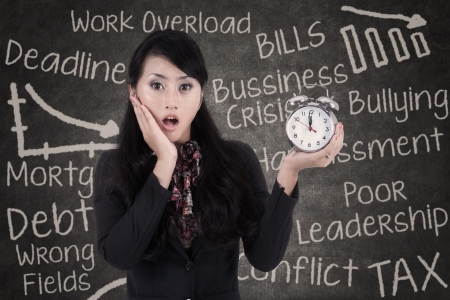 hectic: Shocked businesswoman holding an alarm clock