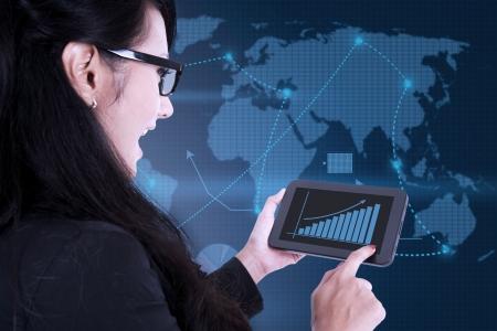 pda: Asian businesswoman using digital touchpad on world map background Stock Photo