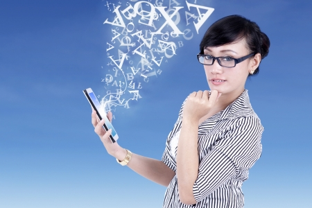 Businesswoman and digital tablet with flying letters on blue photo