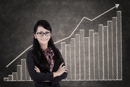 Confident Businesswoman  with growing bar chart in class photo