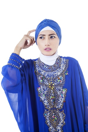 Confused female muslim in blue dress, isolated on white photo